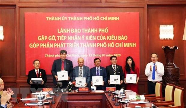 Ông Nguyễn Thiện Nhân, Ủy viên Bộ Chính trị, Bí thư Thành ủy Thành phố Hồ Chí Minh (ngoài cùng bên phải) tặng quà cho đại diện kiều bào tại buổi gặp mặt. (Ảnh: Xuân Khu/TTXVN)