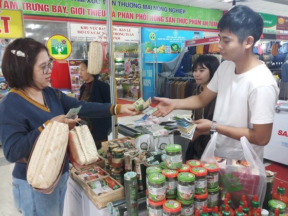 Người dân đi mua sắm tại hội chợ nông nghiệp vừa khai mạc ở Hà Nội