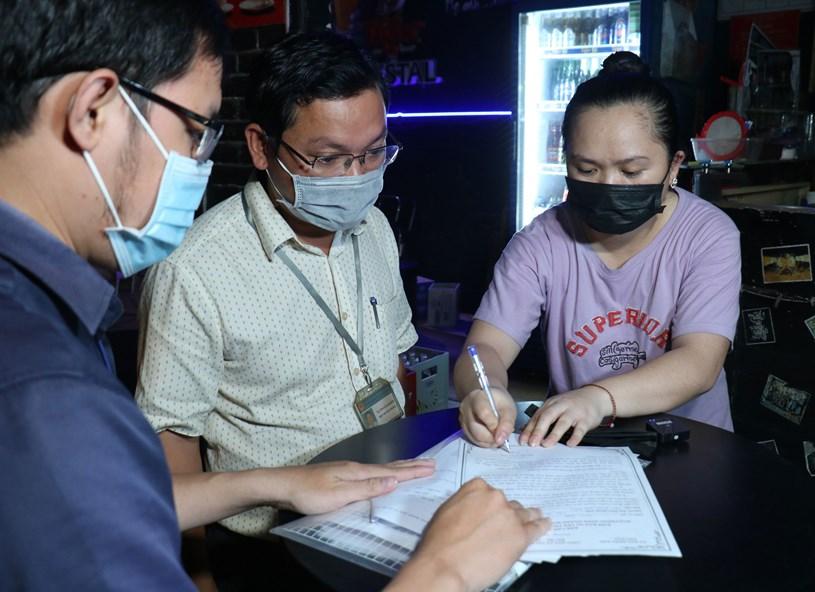 Đoàn kiểm tra quận Bình Thạnh nhắc nhở, tuyên truyền, buộc cơ sở kinh doanh ký cam kết không vi phạm tiếng ồn. Ảnh: THÁI PHƯƠNG/SGGP