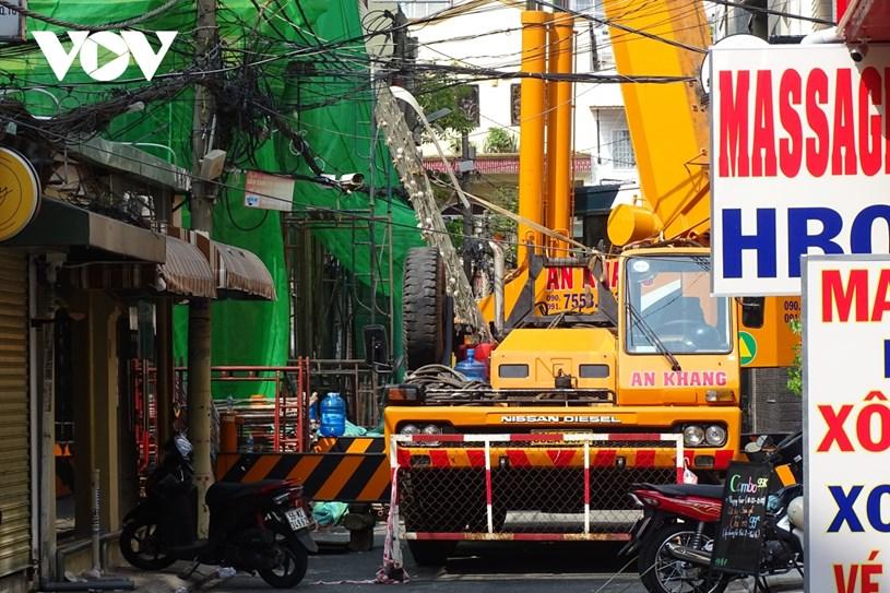 Một chiếc xe cẩu, khoan cắt bê tông được đưa tới công trình, phá dỡ phần hiện trạng xây dựng sai phép.