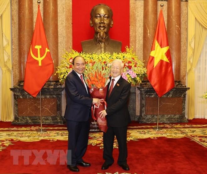 Chủ tịch nước Nguyễn Xuân Phúc tặng hoa Tổng Bí thư Nguyễn Phú Trọng, nguyên Chủ tịch nước.(Ảnh: Trí Dũng/TTXVN)