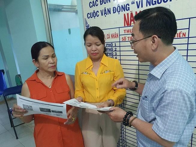 Bà Nguyễn Thị Nhẫn (giữa), Bí thư Đảng ủy phường 13, quận 3, TP.HCM, hướng dẫn người dân sử dụng Cổng thông tin danh sách cử tri quận 3. Ảnh: V.HOA