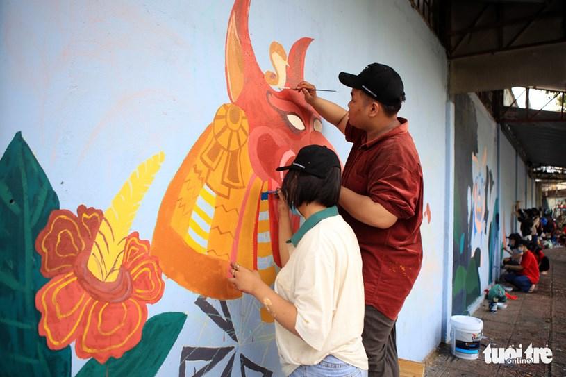 Lê Nguyễn Anh Duy (sinh viên năm nhất, bên phải) tỉ mỉ từng nét vẽ để tái hiện hình ảnh trong bài thi vừa rồi của mình
