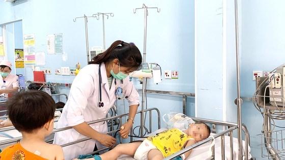 Bác sĩBệnh viện Nhi đồng 1 đang thăm khám và điều trị cho bệnh nhi mắc tay chân miệng. Ảnh:MINH NAM