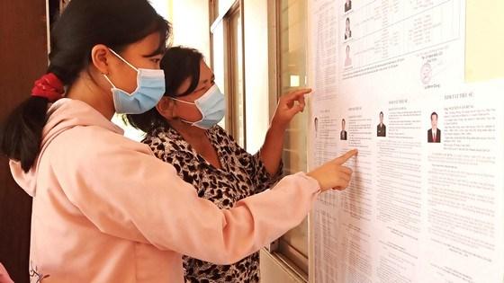 Cử tri thị trấn Cần Thạnh, huyện Cần Giờ, xem danh sách các ứng cử viên. Ảnh: THANH TÂM