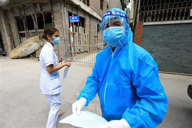 Nhân viên Trung tâm kiểm soát bệnh tật CDC Hà Nội làm thủ tục bàn giao với nhân viên y tế quận Bắc Từ Liêm đưa bệnh nhân F1 đi cách ly tập trung sáng 4/5. (Ảnh: Thành Đạt/TTXVN)