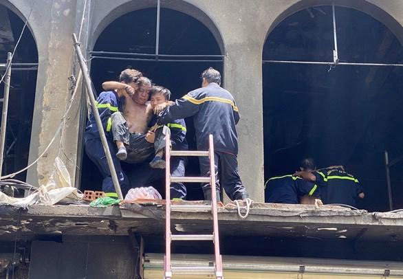 Hai nạn nhân bỏng được lực lượng PCCC đưa ra ngoài - Ảnh: M.H.