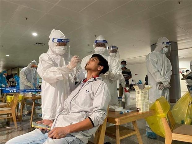 Nhân viên y tế lấy mẫu xét nghiệm cho người làm việc tại sân bay Tân Sơn Nhất. (Nguồn: TTXVN phát)