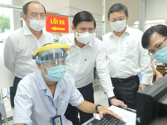 Chủ tịch UBND TP Nguyễn Thành Phong và Phó Chủ tịch UBND TP Dương AnhĐức kiểm trahệ thống khai báo y tế điện tử tại Bệnh viện Nhân dân 115. Ảnh: CAO THĂNG