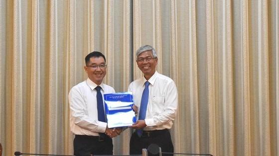 Phó Chủ tịch UBND TPHCM Võ Văn Hoan (bên phải) trao quyết định tới tân Phó Giám đốc Sở Xây dựng TPHCM Huỳnh Thanh Khiết