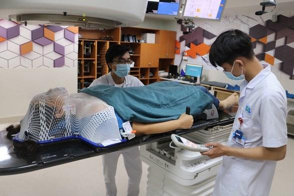 Kỹ thuật viên điều chỉnh máy móc, chuẩn bị xạ trị cho ca ung thư vòm hầu - Ảnh: HOÀNG AN