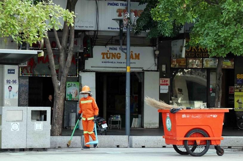 Lực lượng công ích vẫn hoạt động tại khu vực phố đi bộ Nguyễn Huệ (Quận 1). (Ảnh: Xuân Khu/TTXVN)