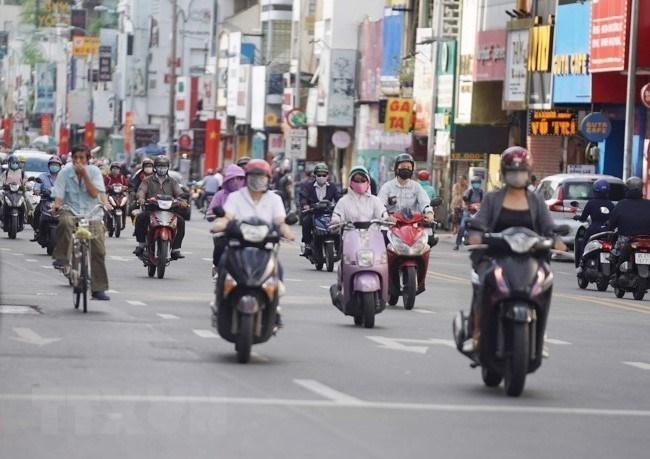 Người dân di chuyển trên tuyến đường Phan Đình Phùng (quận Phú Nhuận) chấp hành đeo khẩu trang khi ra đường nhằm phòng chống dịch COVID-19. (Ảnh: Thu Hương/TTXVN)