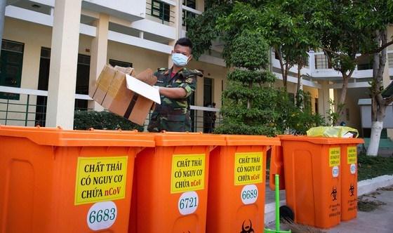 Các chiến sĩ Trường Quân sự Quân khu 7 (quận 12, TPHCM) cẩn thận thu gom, phân loại rác để vào các thùng màu cam chuyên dụng chứa rác độc hại tại khu cách ly. Ảnh: HOÀNG HÙNG