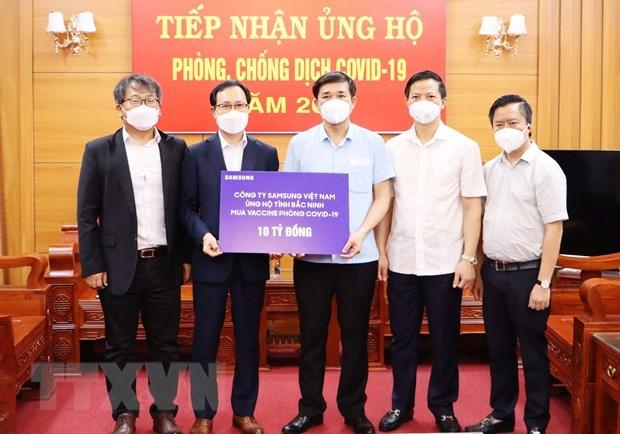 Ông Choi Joo Ho, Tổng Giám đốc Tổ hợp Samsung Việt Nam (thứ 2 từ trái sang) trao hỗ trợ ủng hộ công tác phòng, chống dịch COVID-19 tại tỉnh Bắc Ninh. (Ảnh: Đinh Văn Nhiều/TTXVN)