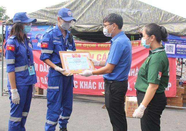 Đoàn công tác do anh Trương Minh Tước Nguyên (bìa trái), Phó Bí thư Thành Đoàn TPHCM đến thăm và động viên lực lượng tình nguyện viên SOS Hướng Nam đang làm việc tại chốt kiểm soát dịch bệnh ở giao lộ Phạm Văn Đồng - Phan Văn Trị (quận Gò Vấp)