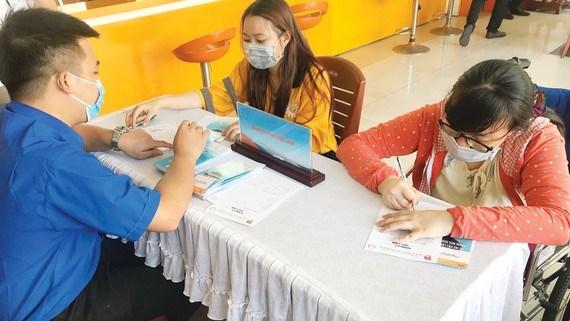 Người lao động bị ảnh hưởng bởi dịch Covid-19 tìm hiểu thông tin, đăng ký tìm việc làm mới tại Trung tâm Dịch vụ việc làm Thanh niên TPHCM. Ảnh: GIA NHI