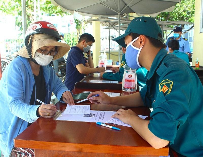 Người dân khai báo y tế khi đến giao dịch hồ sơ tại UBND quận Bình Tân. Ảnh: LÊ THOA