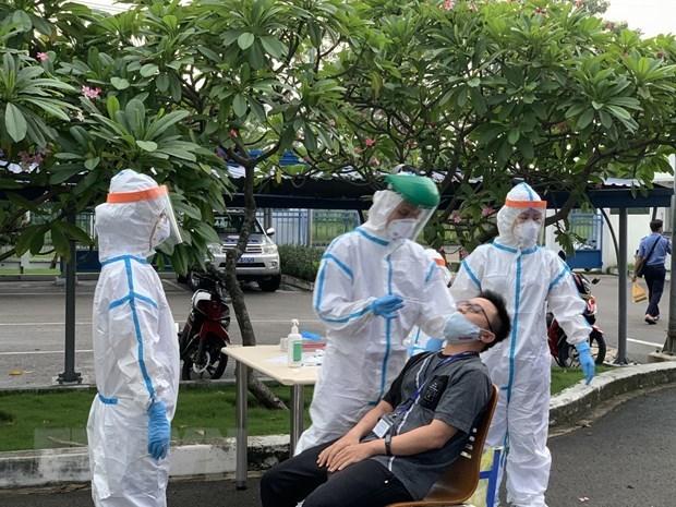 Các y bác sỹ Trung tâm kiểm soát bệnh tậtThành phố Hồ Chí Minhvà Quận 7 thực hiện xét nghiệm sàng lọc COVID-19 ngẫu nhiên cho công nhân. (Ảnh: Thanh Vũ/TTXVN)