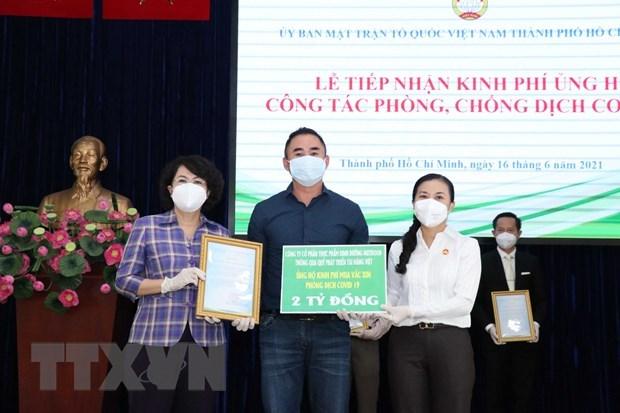 Bà Phan Kiều Thanh Hương, Phó Chủ tịch Ủy ban Mặt trận Tổ quốc Việt Nam TP.HCM (bên phải), tiếp nhận bảng tượng trưng ủng hộ công tác phòng, chống dịch COVID-19 của Ban Liên lạc truyền thồng Trường Sơn, Thành phố Hồ Chí Minh. (Ảnh: Xuân Khu/TTXVN)