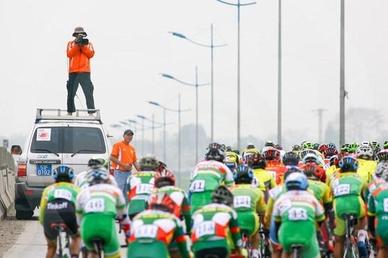 Để góc quay sinh động hơn trong một buổi tường thuật cuộc đua xe đạp Cúp Truyền hình TPHCM, phóng viên truyền hình sáng tạo tác nghiệp theo cách chỉ riêng mình ta. Ảnh: HOÀNG HÙNG