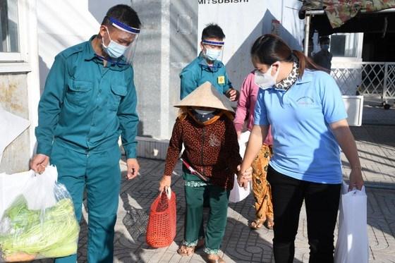 Hỗ trợ người dân đến nhận quà. Ảnh: MTTQ Bình Tân