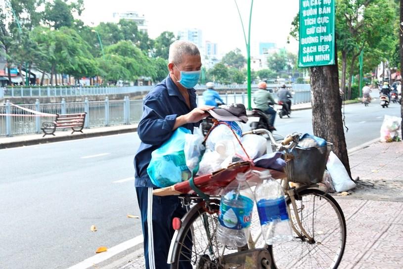 Chú Hải dừng xe ve chai của mình bên lề đường để ghé vào nhận những phần thực phẩm tươi sống