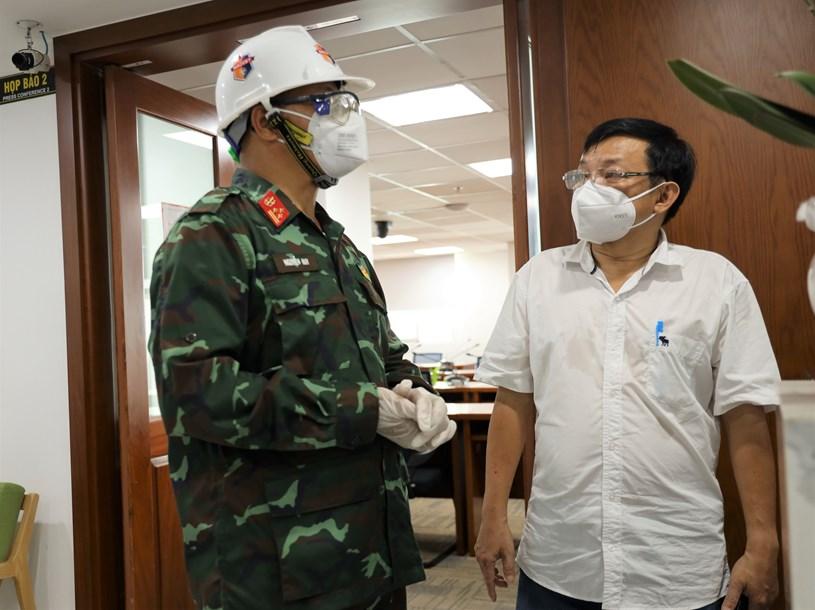 Phó Lữ đoàn trưởng Lữ đoàn Phòng hóa 87 Nguyễn Huy và Phó Giám đốc Trung tâm Báo chí TP Nguyễn Văn Khanh trao đổi phương án phun khử khuẩn tại Trung tâm