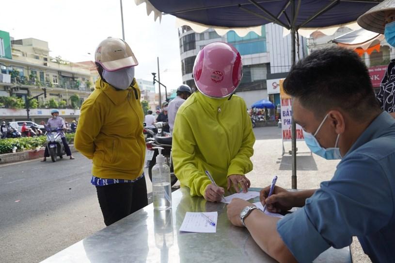 Người dân đi chợ phải xếp hàng khai báo y tế, được kiểm tra thân nhiệt và cấp phiếu ra vào chợ.