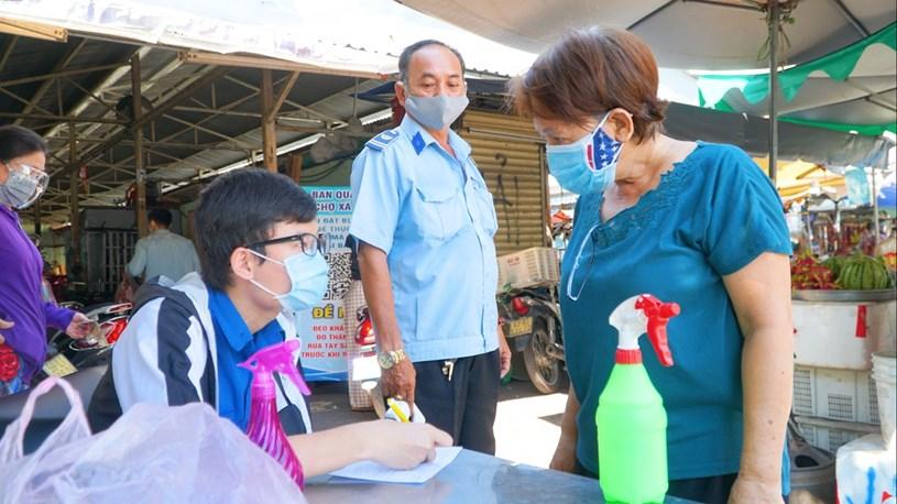 Khách phải khai báo y tế, đo thân nhiệt và rửa tay khử khuẩn trước khi vào chợ/ LÊ NAM
