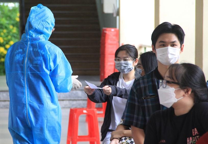 Sinh viên tình nguyện chương trình Tiếp sức mùa thi mặc đồ bảo hộ, đeo găng tay khi làm nhiệm vụ tại trường THCS Huỳnh Tấn Phát