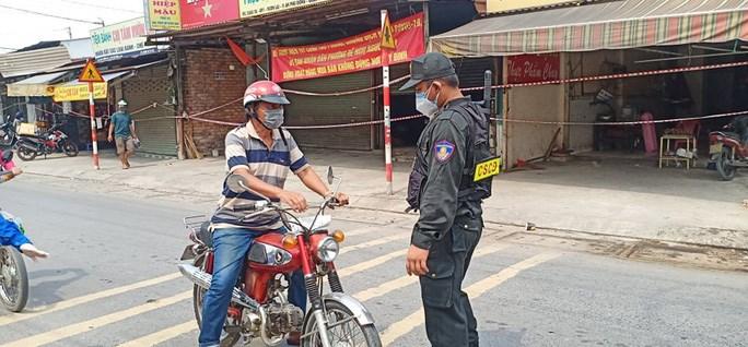 Lực lượng cảnh sát cơ động kiểm tra người đi đường tại quận 12