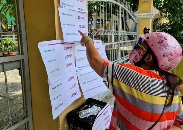 Bảng giá niêm yết được dán trên bờ rào trường tiểu học - Ảnh: NGỌC HIỂN