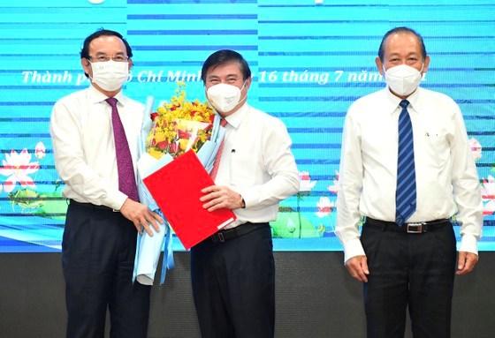 Bí thư Thành ủy TPHCM Nguyễn Văn Nên tặng hoa chúc mừng đồng chí Nguyễn Thành Phong. Ảnh: VIỆT DŨNG