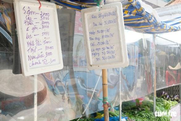 Tiểu thương chợ Ngã Ba Bầu (quận 12) treo bảng giá, giúp khách hàng thuận tiện mua hàng - Ảnh: BÔNG MAI