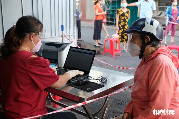 Người dân phải khai báo thông tin để được nhận thẻ ra vào chợ có in mã QR, nhằm thuận tiện truy vết - Ảnh: BÔNG MAI