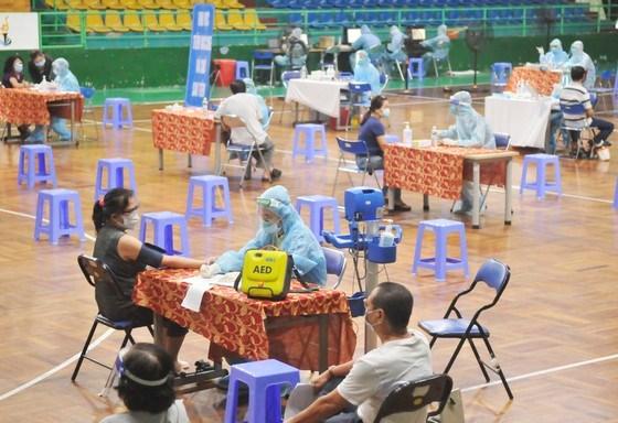 Kiểm tra sức khỏe người dân trước khi tiêm vaccine tại điểm tiêm Nhà thi đấu Lãnh Binh Thăng, quận 11, TPHCM, sáng 22-7-2021. Ảnh: CAO THĂNG