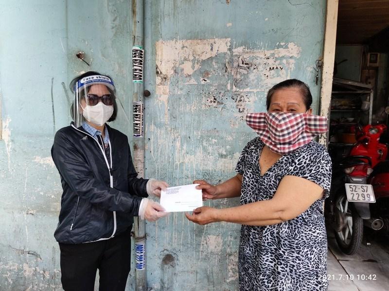 Bà Triệu Thị Bích Huyền (trái), Phó chủ tịch UBND phường 11, quận Bình Thạnh trao tiền hỗ trợ cho người dân. Ảnh: NGUYỄN HIỀN