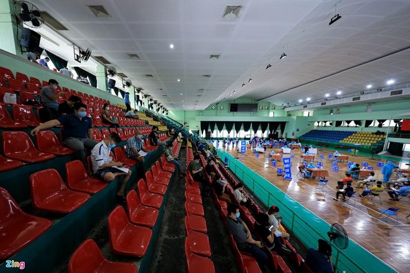 Bên trong nhà thi đấu, ban tổ chức tăng cường tuyên truyền bằng việc bố trí nhiều loa phát thanh liên tục nhắc nhở người dân giãn cách, trật tự, chờ tới lượt.