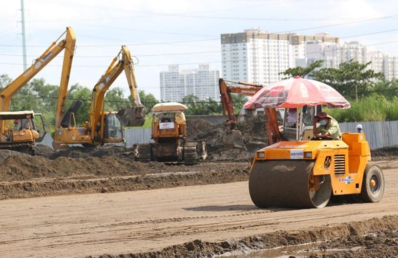 San ủi nền đất để xây dựng khu mở rộng tại bệnh viện dã chiến trên đường Nguyễn Văn Linh. (Ảnh: Trần Xuân Tình/TTXVN)