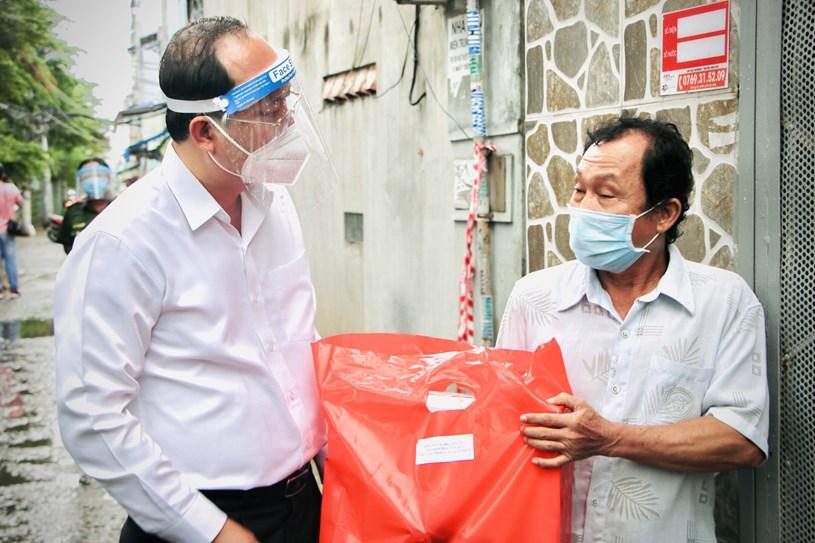 Phó bí thư Thành ủy TP.HCM Nguyễn Hồ Hải thăm hỏi, động viên người dân tại hẻm 76 Tôn Thất Thuyết, quận 4 - Ảnh: CHÂU TUẤN
