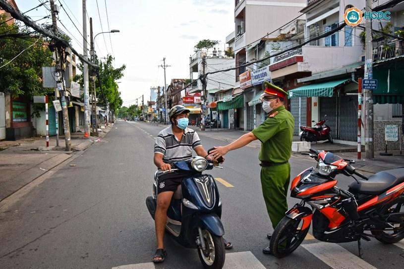 Lực lượng chức năng nhắc nhở người dân không ra đường sau 18 giờ trên đường Phạm Thế Hiển, Quận 8