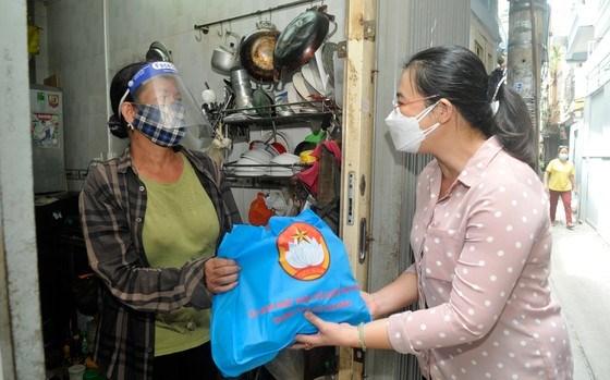 Đại diện Ban Dân vận Thành ủy TPHCM thăm hỏi, tặng quà tại hẻm 808 Cách Mạng Tháng 8. Ảnh: CAO THĂNG