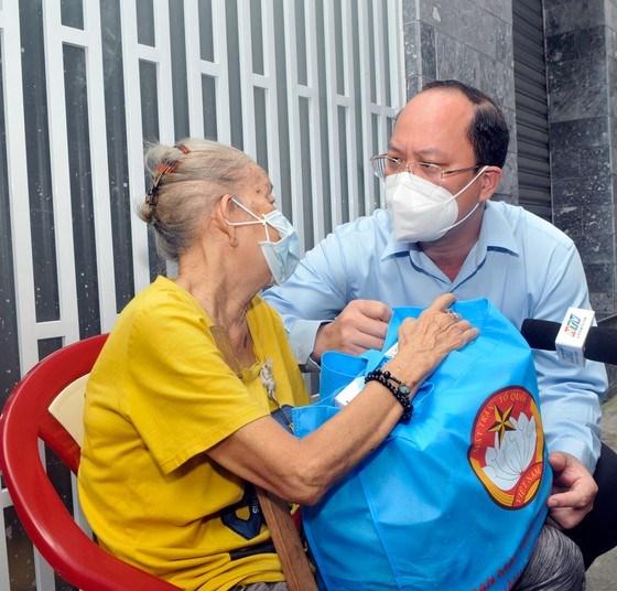 Phó Bí thư Thành ủy Nguyễn Hồ Hải thăm hỏi, động viên người dân tại hẻm 808 Cách Mạng Tháng 8. Ảnh: CAO THĂNG