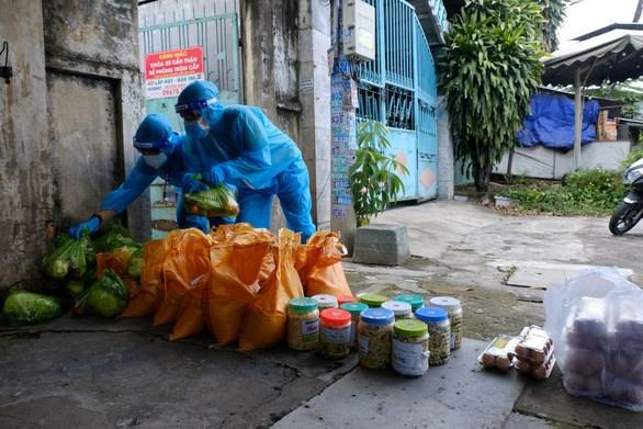 Các thành viên của Ủy ban Mặt trận Tổ quốc Việt Nam TP Thủ Đức đưa hàng cứu trợ đến các khu nhà trọ bị phong tỏa - Ảnh: VŨ THỦY
