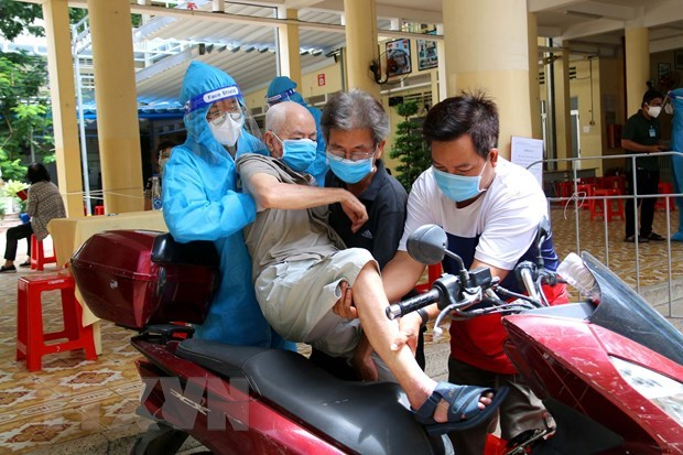 Các y, bác sỹ Quận 3 cùng người nhà hỗ trợ người cao tuổi đến tiêm vaccine tại điểm tiêm trường tiểu học Trần Quốc Thảo. (Ảnh: Thanh Vũ/TTXVN)