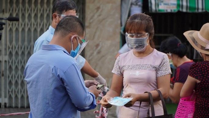 Nhân viên chợ Bình Thới (quận 11) kiểm tra thông tin trước khi hướng dẫn khách hàng vào chợ mua sắm