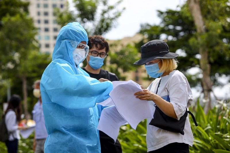 Trước khi tiêm, phường đã bố trí tình nguyện viên hướng dẫn người dân khai thông tin.