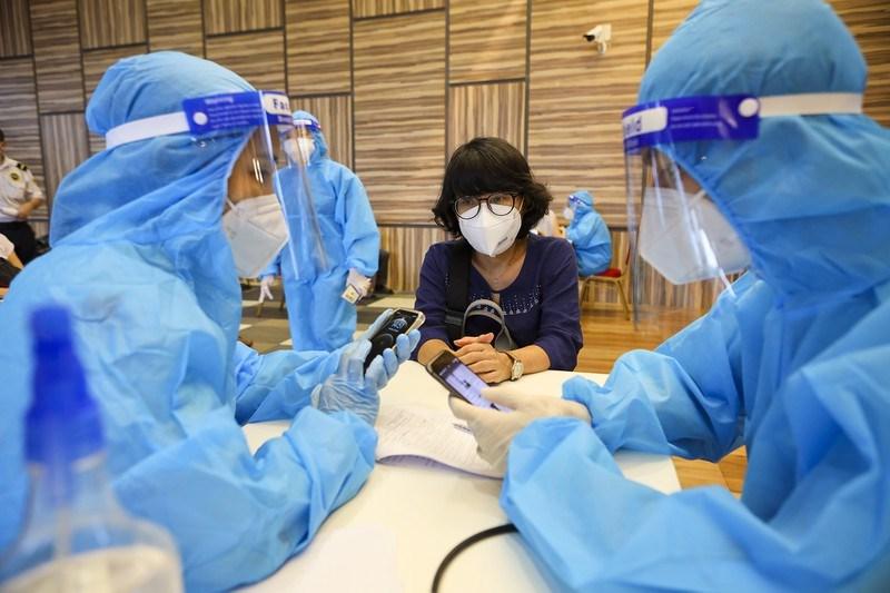 Bàn thăm khám sàng lọc gồm một nhân viên y tế và một người phiên dịch để kiểm tra cho người được tiêm.
