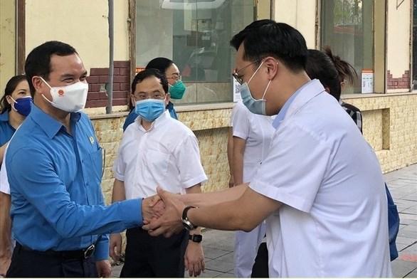 Chủ tịch Tổng liên đoàn Lao động Việt Nam Nguyễn Đình Khang (bìa trái) động viên bác sĩ Bệnh viện Hữu nghị Việt Đức lên đường vào hỗ trợ TP.HCM chống dịch - Ảnh: ĐẶNG LỢI